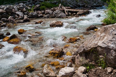Mountain stream flowing over yellow rocks Royalty Free Stock Photo