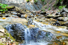 A mountain stream flowing between stones Royalty Free Stock Image