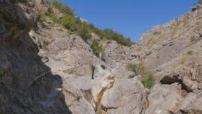 Mountain stream flowing through stones stock footage