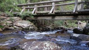Mountain Stream Flowing Under Hiking Bridge 01. A mountain stream, the St Vrain Creek, flows underneath a bridge on the Thunder Lake Trail in Rocky Mountain stock video footage