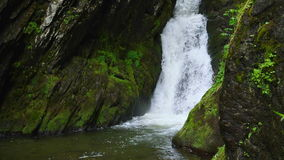 The mountain stream flows downward with cascades stock video footage