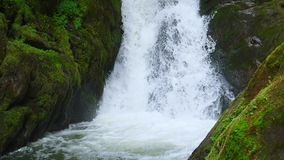 The mountain stream flows downward with cascades stock footage