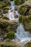 The mountain stream flows throw the stones with a beautiful flow. A view of the mountain stream flowing in cool streams along the rocks among the green grass and Stock Image