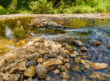 Mountain stream in a forest. Yellow rocks are seen through the clear water flowing, Khao Sok National Park, Surat Thani Province, Thailand Royalty Free Stock Photos