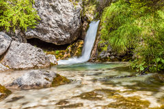Mountain stream forms a waterfall Stock Image