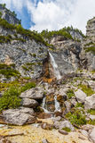 Mountain stream forms a waterfall Royalty Free Stock Photo
