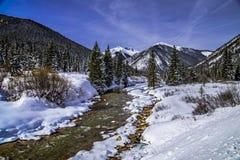 Mountain stream with fresh snow on sunny day stock photo