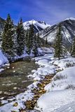 Mountain stream with fresh snow on sunny day stock images