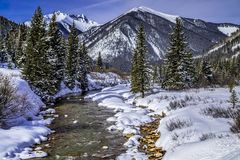 Mountain stream with fresh snow on sunny day royalty free stock photo