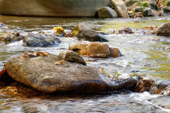 Mountain stream in Khao Sok National Park, Surat Thani Province, Thailand. Selective focus on a large rock in the foreground Royalty Free Stock Images