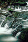 Mountain Stream over Mossy Rocks. Mountain stream flowing over moss covered rocks, blurred water Royalty Free Stock Photo