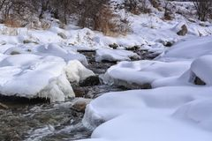 Mountain stream. Mountain stream among the snow and stones in the winter Stock Photo