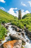 Mountain stream and watch tower in the village Adishi, Georgia Royalty Free Stock Images