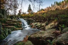 Mountain stream with waterfall in an autumn forest. Royalty Free Stock Image