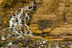 Mountain stream waterfall. Mountain stream and waterfall surrounded by stones and rocks Royalty Free Stock Image