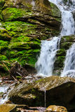 Mountain stream on wet rocks with moss. Rugged mountain stream with large cascades. Wet large rocks covered with moss Stock Photography
