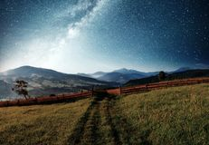 Mountain summer landscape. High grass and vibrant night sky with stars and nebula and galaxy. Deep sky astrophoto.  stock images
