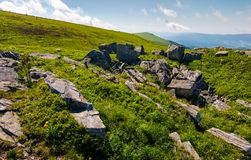 Huge rocks on top of mountain ridge. Mountain summer landscape. meadow with huge rocks among the grass on top of the hillside near the peak of mountain ridge royalty free stock image