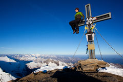 Mountain summit. Young man sitting on a summit cross in the Alps Royalty Free Stock Photo