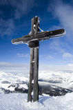 Mountain Summit. Cross on a snow covered mountain summit in winter with blue Stock Photo