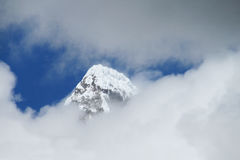 Mountain summit in clouds. High peaks covered with blue ice and white snow. Icefalls, massive snow blocks on the mountain summit Stock Photography