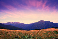 Mountain sunrise with pink and violet clouds Stock Images