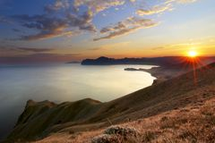 Mountain sunset. Majestic sunset in the mountains above the sea Stock Image