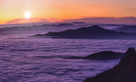 Mountain sunset above clouds. Romanian landscape in Carpathians with mystic cloud sea Royalty Free Stock Image