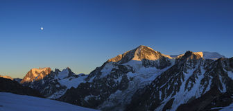 Mountain sunset. Evening with full moon in the Swiss Alps with a majestic view on Mont Collon royalty free stock photos