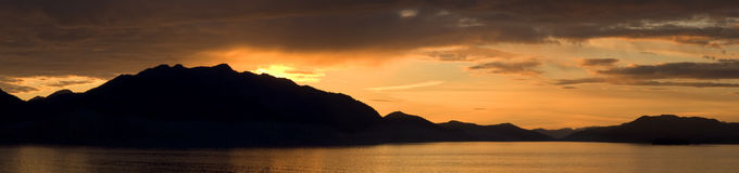 Mountain Sunset Panorama. Mountains in Alaska silhouetted by sunset Stock Image