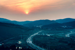 Mountain sunset scenery. Through the mountains to a highway in the afterglow Royalty Free Stock Photo