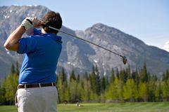 Mountain Swing. A golfer makes a shot along the fairways of Kananaskis Golf Course royalty free stock photography