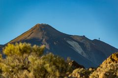 Mountain Teide with funicular facilities on the right slope. Bright blue saturated sunset sky. Blurred endemic plants in the royalty free stock photo
