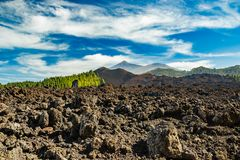 Mountain Teide, partly covered by the clouds. Bright blue sky above the pine forest and lava rocks. Teide National Park, Tenerife royalty free stock photo