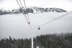 Mountain top cable cars. Cable cars travelling between two snowy mountain tops above snow covered trees and through the low clouds Stock Photos