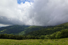 Mountain top with green meadows in the rain clouds Royalty Free Stock Photography