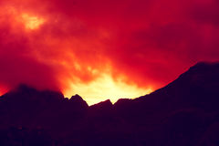 Mountain top outlined with cloudy sunset sky. Burned red sunset. Beautiful nature Norway. Lofoten islands. Reine Royalty Free Stock Image