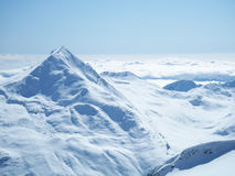 Mountain top over clouds. The snow covered mountain top peeking through a sea of clouds near near Saas-Fee Switzerland stock image