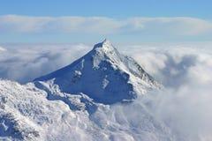 Mountain top peeking through clouds. A steep rocky mountain top peeking through a sea of clouds stock photos