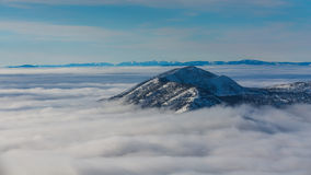 Mountain top poking up through clouds. Snowy mountain top poking up through cloud inversion on a blue sky day in Canada stock photo