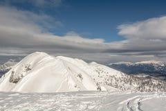 Mountain top with ski tracks. Leading down Stock Photo