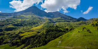 Mountain top in Swiss Alps in summer. Idyllic mountain top with green pastures under a blue sky with white clouds. High up in the Swiss Alps in summer. Val d` royalty free stock photography