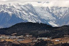 Meili Snow Mountain and village. The mountain top under the cloudy sky.Meili Xue Shan or Mainri Snow Mountain is a mountain range in the Chinese province of royalty free stock photography
