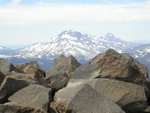 Mountain Top View. The view of Three Sisters high atop of Mt. Bachelor in Central Oregon. The rocks in the foreground are the peak of Mt. Bachelor. Mt. Bachelor royalty free stock photos
