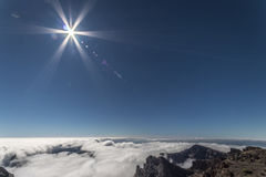 Mountain top view with clouds & blue sky. Dramatic sun flare against a crystal clear blue sky from a mountain top at a high altitude, above the white fluffy Stock Image
