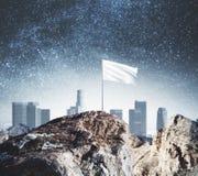 Mountain top with white flag Stock Image
