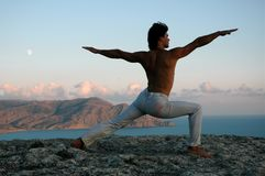 Mountain Top Yoga. Young man practicing yoga on a scenic, high mountain top overlooking the Black Sea in Crimea, Ukraine Stock Photo
