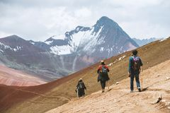 Mountain tourism in Peru. VINICUNCA, PERU - OCTOBER 29: three tourists hiking by altitude mountain trail near Vinicunca area, Peru on October 29, 2018 stock photo