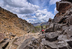 Mountain tourism. Woman overcomes part of the way to large boulders Royalty Free Stock Photography