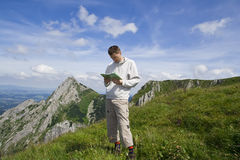 Mountain tourist looking into map over blue sky Stock Photos
